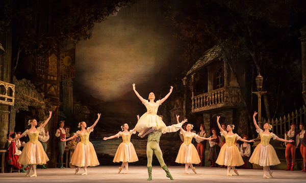 A male ballet dancer holds a female aloft in front of a group of female dancers