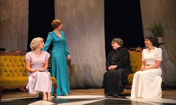 Four women in thirties costume, three seated, one standing