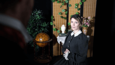 A Victorian lady looks demurely out, past a shadowy figure