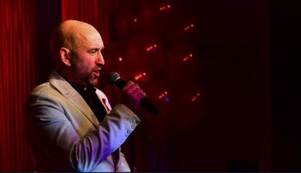 Bald man singing into microphone