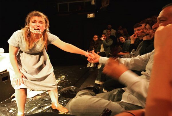 Woman with messy face being dragged into audience