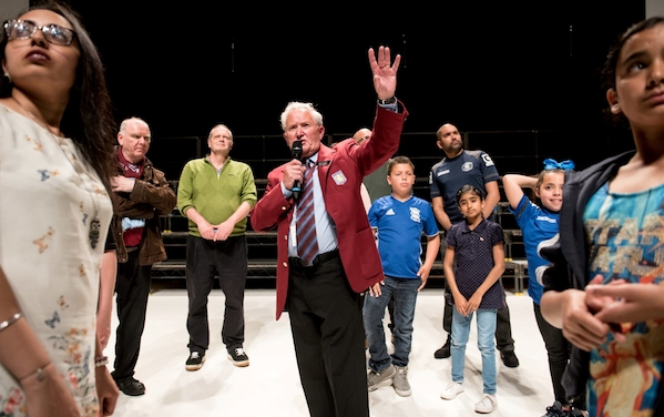A man ina red jacket is speaking to a tour group on a white stage and black background
