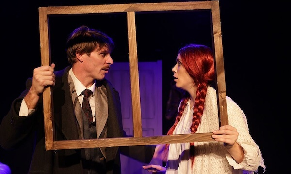 A man and woman look at each other while holding a window frame up