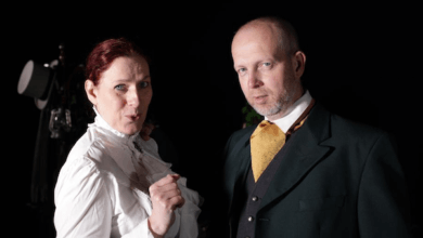 A man and woman in Victorian dress look out of the picture
