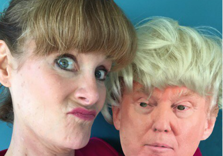 woman holding donal trump mask with wig on