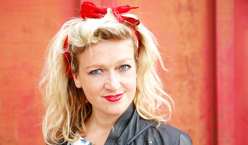 blonde woman with black leather jacket and red bow in hair
