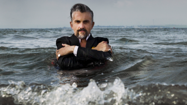 man dressed in suit up to shoulders in the sea