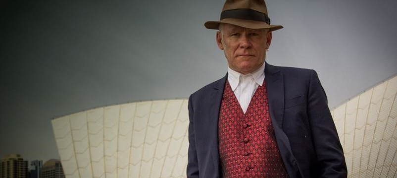 man in jacket waistcoat and hat stares at camera