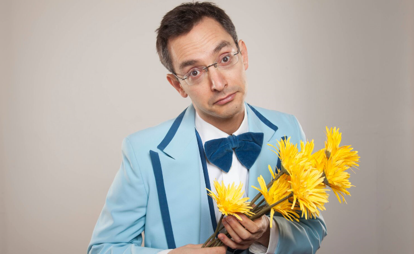 man in pale blue suit holding yellow flowers