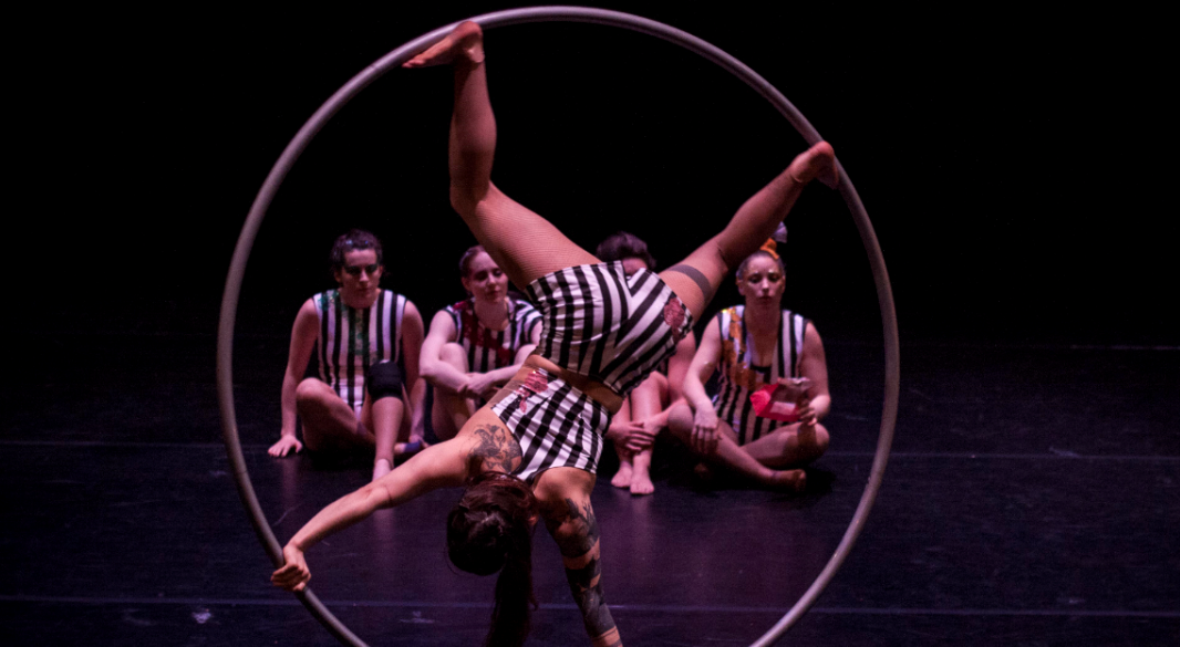 woman in striped leotard rotatimng on a giant hoop in front of fellow circus performers