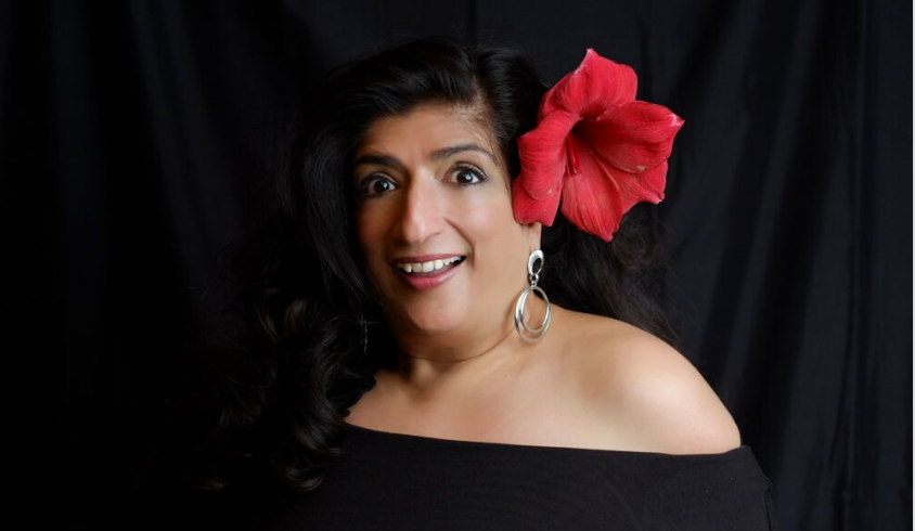 woman dressed in black with red flower in her hair