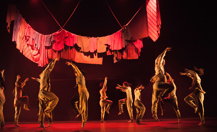 dancers under a ragged red banner
